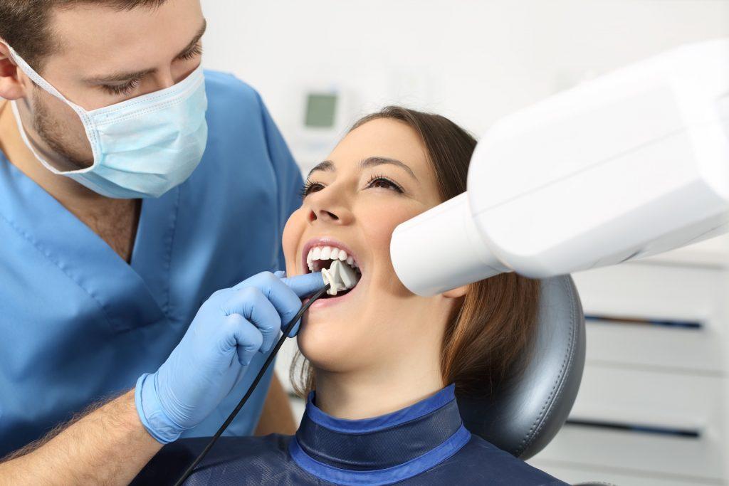دندانپزشک در حال استفاده از سنسور rvg برای بیمار