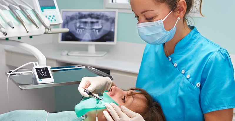 دندانپزشک در حال استفاده از اپکس لوکیتور برای درمان اندو